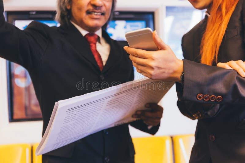 Dos empresarios que leen y que discuten noticias Un periódico que se sostiene mientras que las otras noticias modernas que se con imagen de archivo