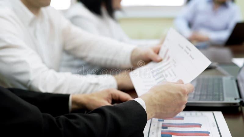Dos encargados que llevan a cabo el documento del informe, estrategia de la compañía que se convierte, negocio foto de archivo libre de regalías