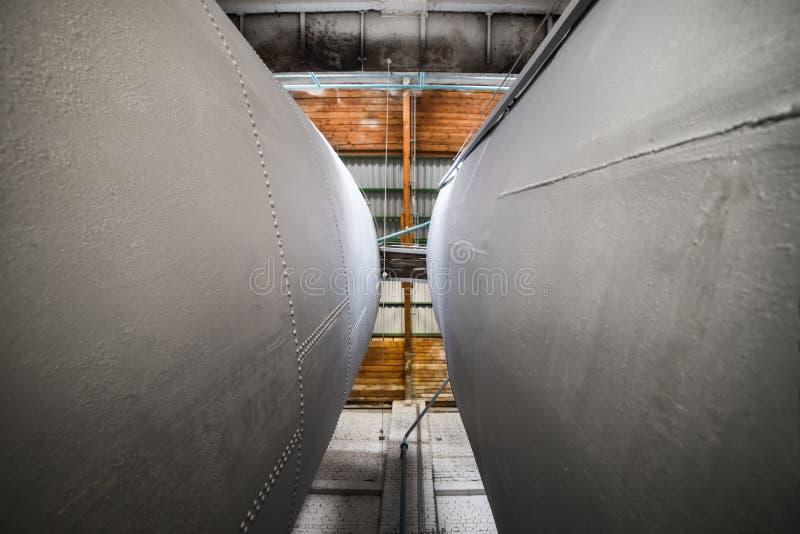 Dos enormes, cisterna alta del metal instalada dentro del edificio imagen de archivo libre de regalías