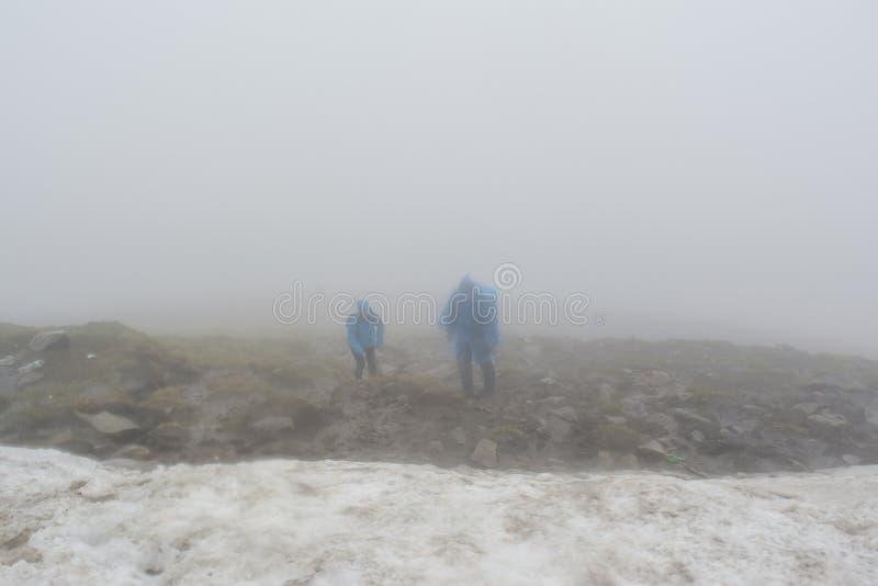 Dos escaladores que suben a la montaña durante mañana de niebla imagen de archivo