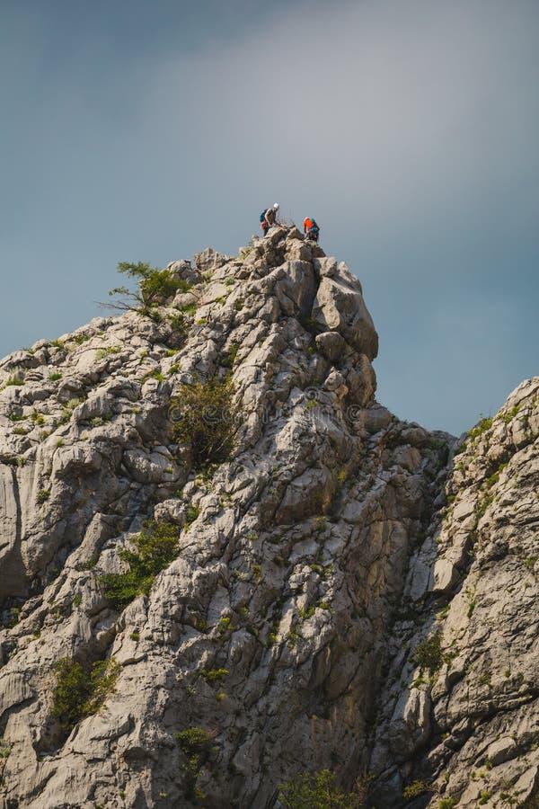 Dos escaladores suben al top de la montaña imagen de archivo