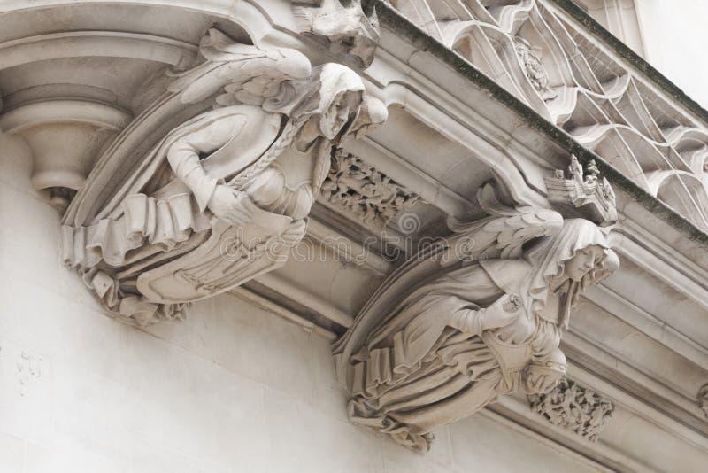 Dos esculturas en la fachada del Tribunal Supremo del Londres que representa dos ángeles que guardan los símbolos de la justicia fotos de archivo libres de regalías