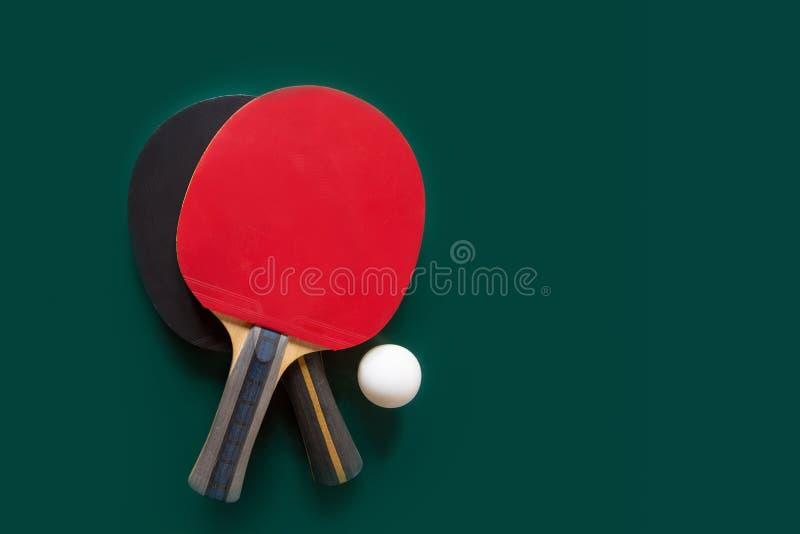 Dos estafas del ping-pong y una bola en una tabla verde foto de archivo