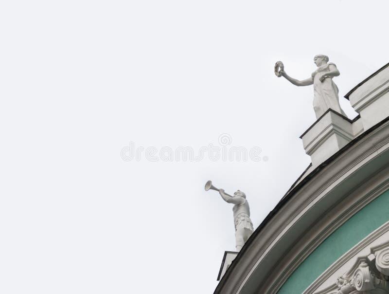 Dos estatuas blancas antiguas en una casa vieja verde aislada en el w foto de archivo libre de regalías