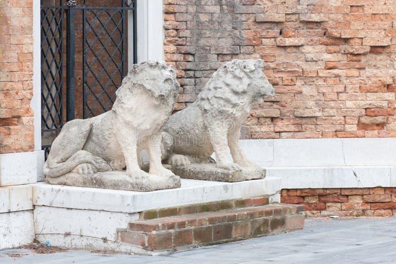 Dos estatuas viejas de los leones delante de una casa vieja en la isla de Murano, cerca de Venecia, Italia imagen de archivo