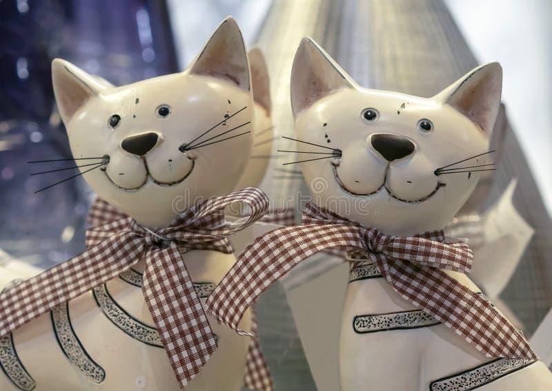Dos estatuillas de gatos sonrientes con los arcos en la tienda de regalos foto de archivo