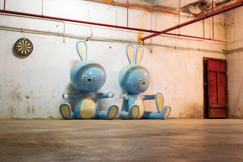 Dos estatuillas gigantes del conejo cerca de una puerta oxidada, en un sótano La una muñeca del conejo con un oído quebrado y  imágenes de archivo libres de regalías