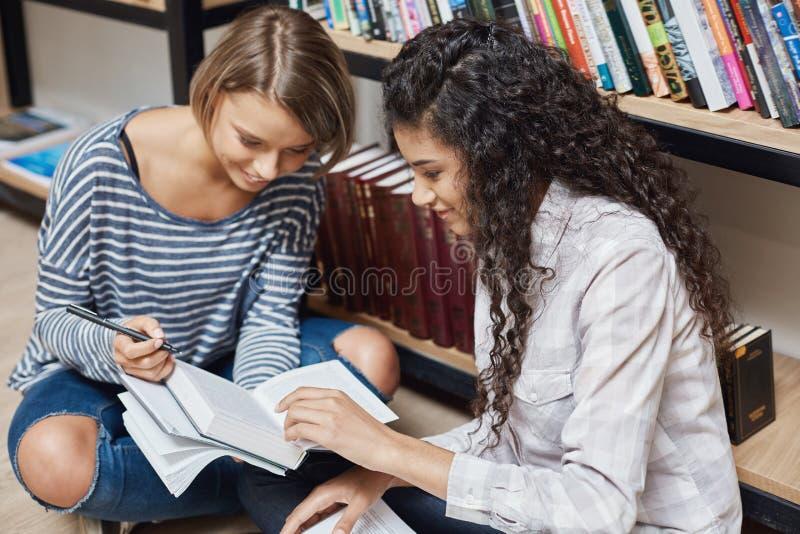 Dos estudiantes étnicos multi femeninos más acertados en la ropa casual que se sienta en piso en la biblioteca de universidad, pr fotos de archivo