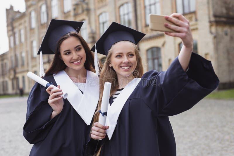 Dos estudiantes bonitos que toman el selfie en día de graduación imagen de archivo libre de regalías