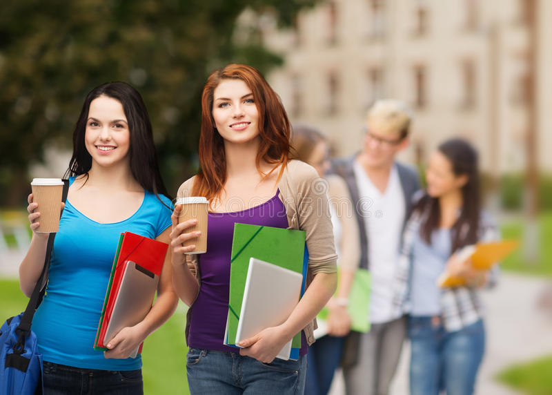 Dos estudiantes con el bolso, las carpetas, la tableta y el café fotos de archivo libres de regalías