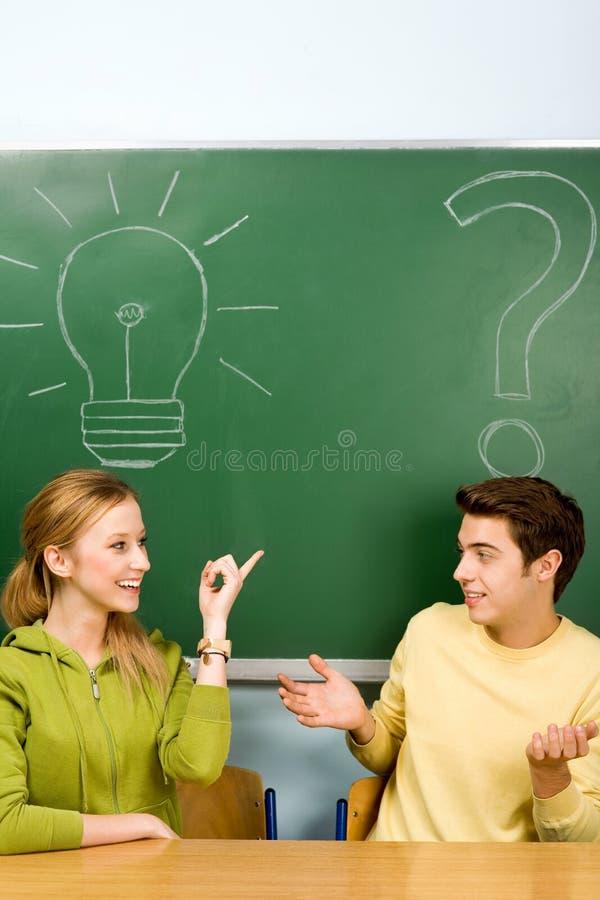 Dos estudiantes con la bombilla y el signo de interrogación foto de archivo libre de regalías