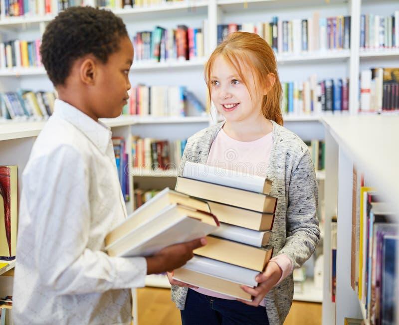 Dos estudiantes con una pila de libros imágenes de archivo libres de regalías