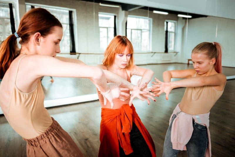 Dos estudiantes de una escuela de danza y su profesor que trabaja en movimientos de las manos imagenes de archivo