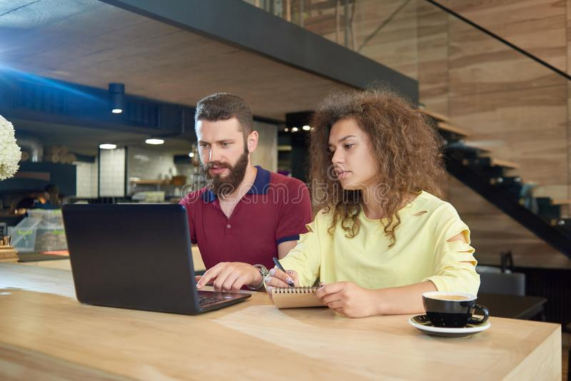 Dos estudiantes jovenes que trabajan para el proyecto educativo que se sienta en café fotos de archivo