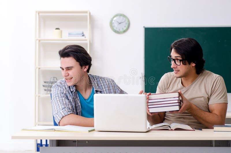 Dos estudiantes masculinos en la sala de clase fotografía de archivo