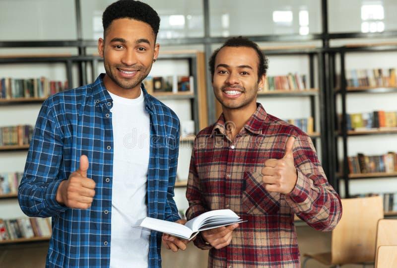 Dos estudiantes masculinos multiculturales sonrientes que consiguen listos para los exámenes fotografía de archivo libre de regalías