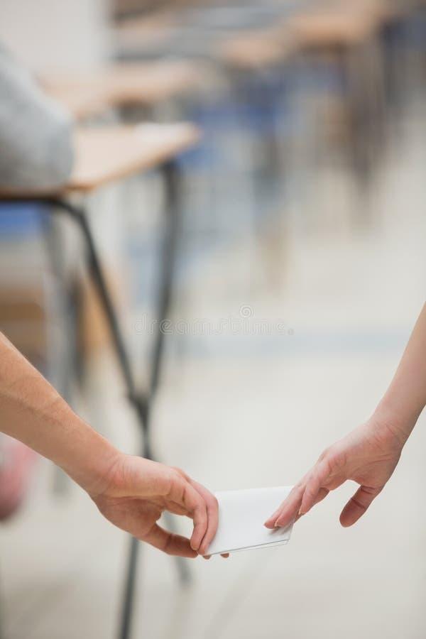 Dos estudiantes que engañan mientras que hace una prueba foto de archivo libre de regalías