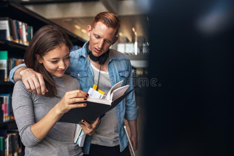 Dos estudiantes universitarios jovenes en biblioteca imágenes de archivo libres de regalías