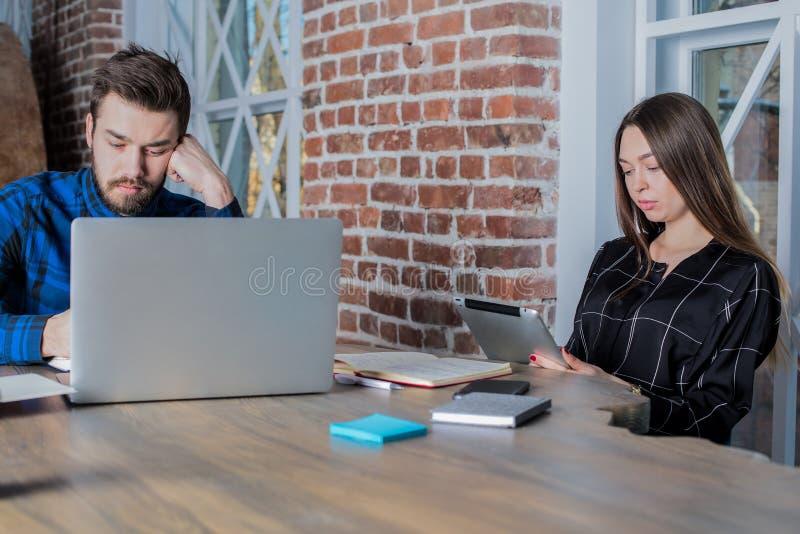 Dos estudiantes universitarios que aprenden en línea vía el red-libro y la tableta digital, sentándose en espacio de co-trabajo fotos de archivo libres de regalías
