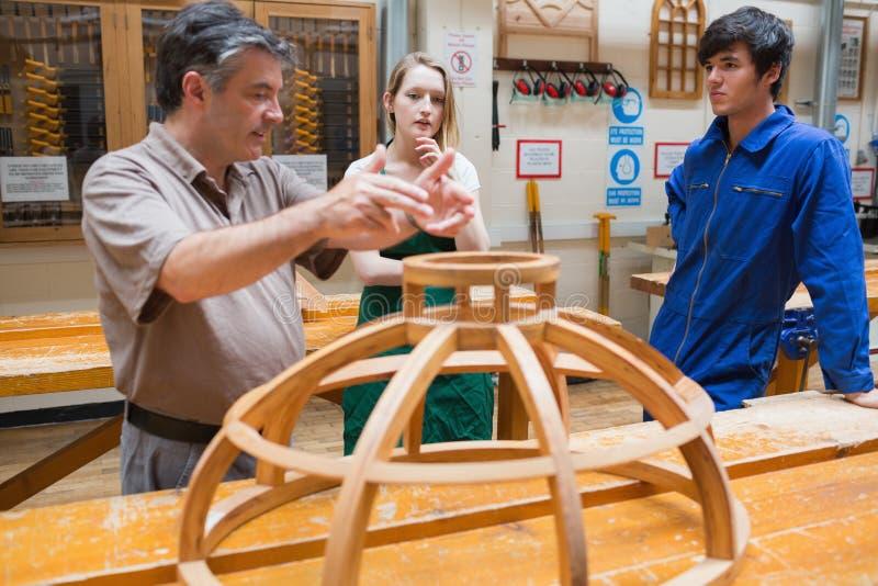 Dos estudiantes y un profesor de explicación en una artesanía en madera clasifican foto de archivo