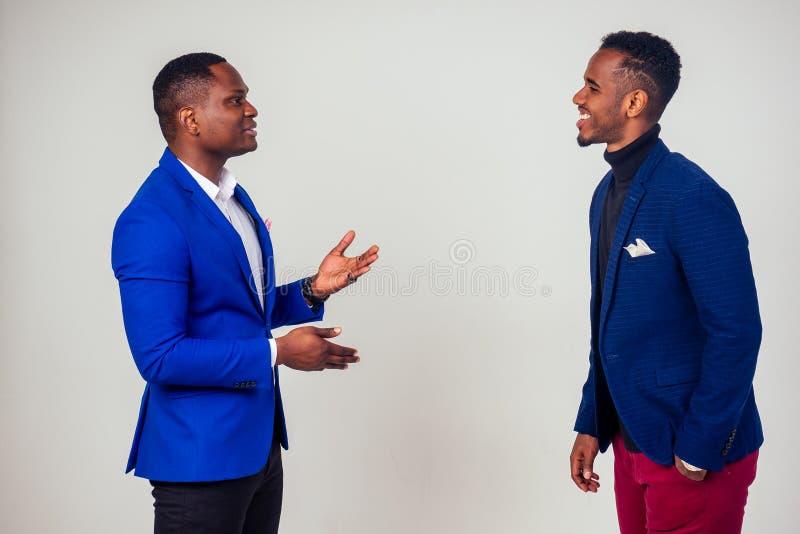Dos exitosos empresarios afroamericanos que se comunican en estudio de fondo blanco fotografía de archivo