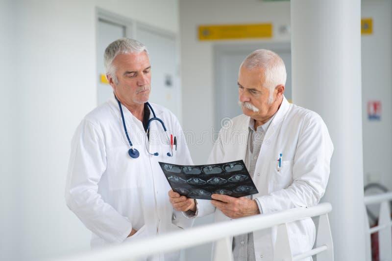 Dos experimentaron a los doctores de sexo masculino que discutían radiografías en corridorb del hospital fotos de archivo libres de regalías