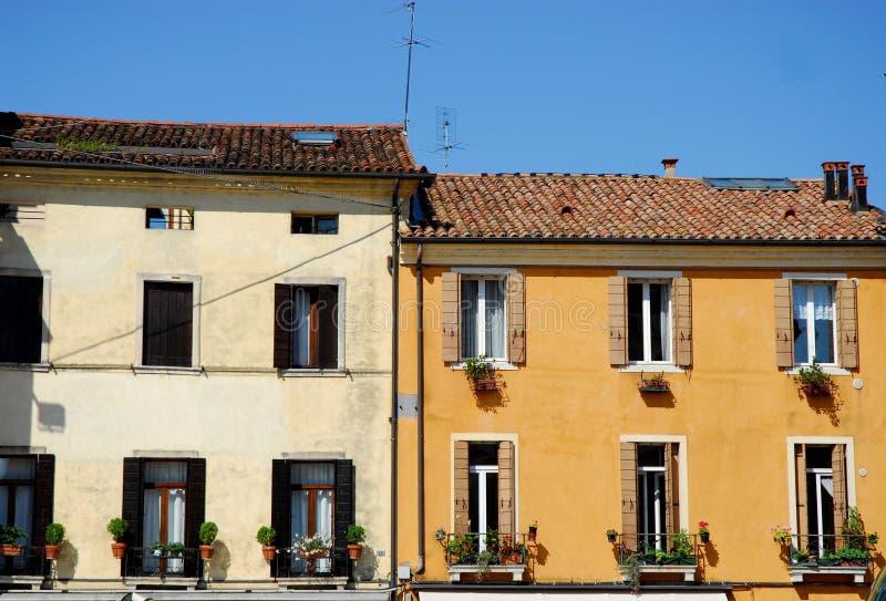 Dos fachadas de casas con las flores delante de la basílica de St Anthony en Padua en el Véneto (Italia) imagenes de archivo