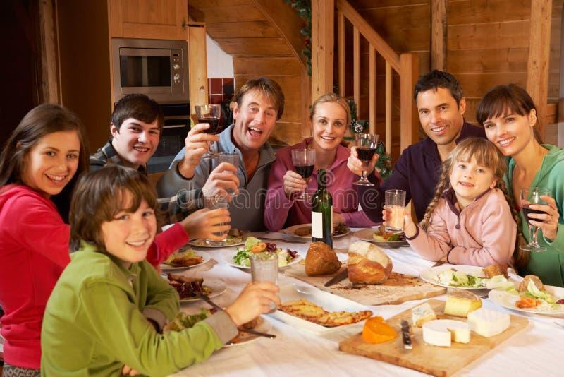Dos Familes que disfruta de la comida en chalet alpestre imágenes de archivo libres de regalías