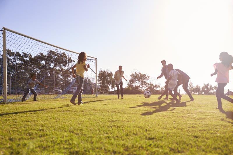 Dos familias que disfrutan de un partido de fútbol con sus niños foto de archivo