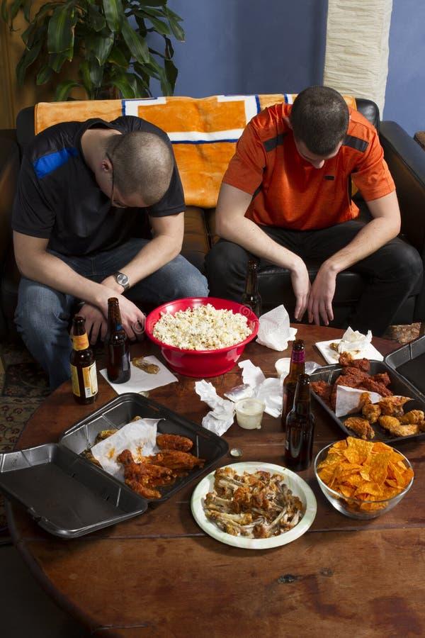 Dos fans de deportes decepcionados que miran el juego de los deportes en la TV, vertical imagen de archivo