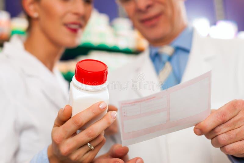 Dos farmacéuticos en la consulta de la farmacia fotografía de archivo libre de regalías