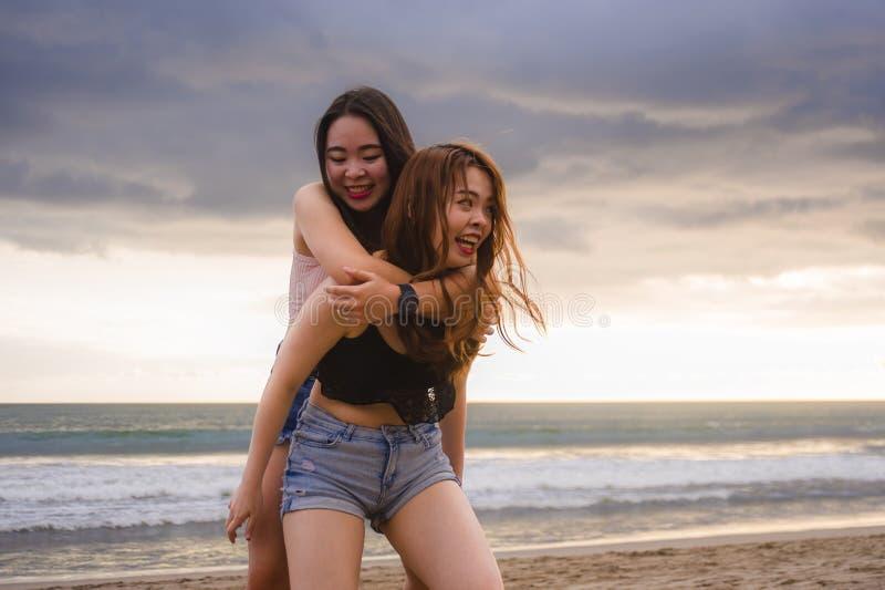 Dos felices y novias o hermanas chinas asiáticas jovenes atractivas de las mujeres que se divierten que juega en el mar en la pla foto de archivo