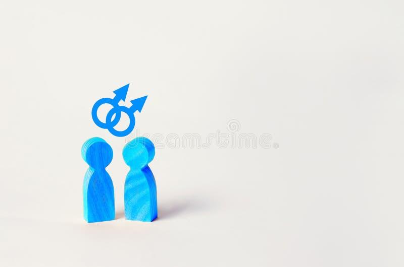 Dos figuras de madera azules de la gente se colocan en el fondo blanco dos personas de orientación homosexual el concepto de betw imagen de archivo