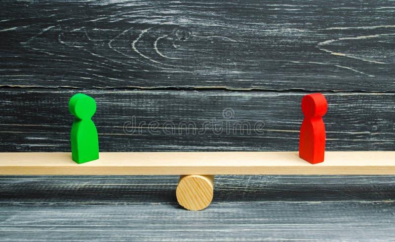 Dos figuras de madera se colocan en las escalas de la justicia rivales Concepto del negocio de beneficio mutuo y éxito de socios  foto de archivo