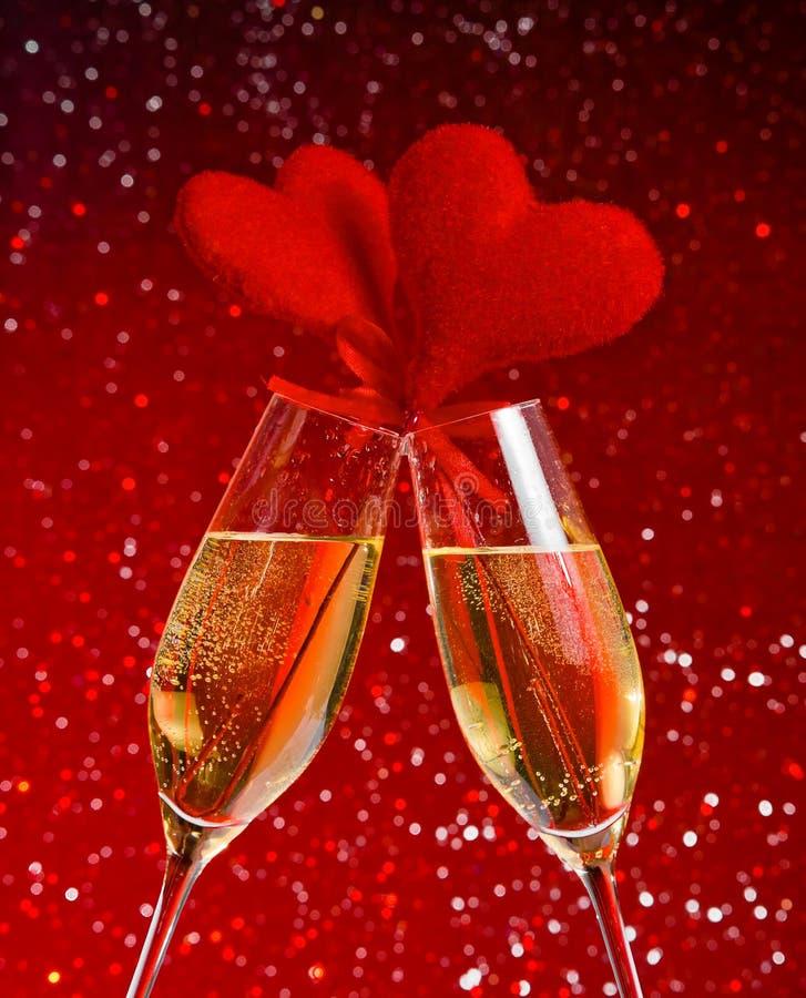 Dos flautas de champán con las burbujas de oro y los corazones rojos del terciopelo hacen alegrías en fondo rojo del bokeh fotos de archivo