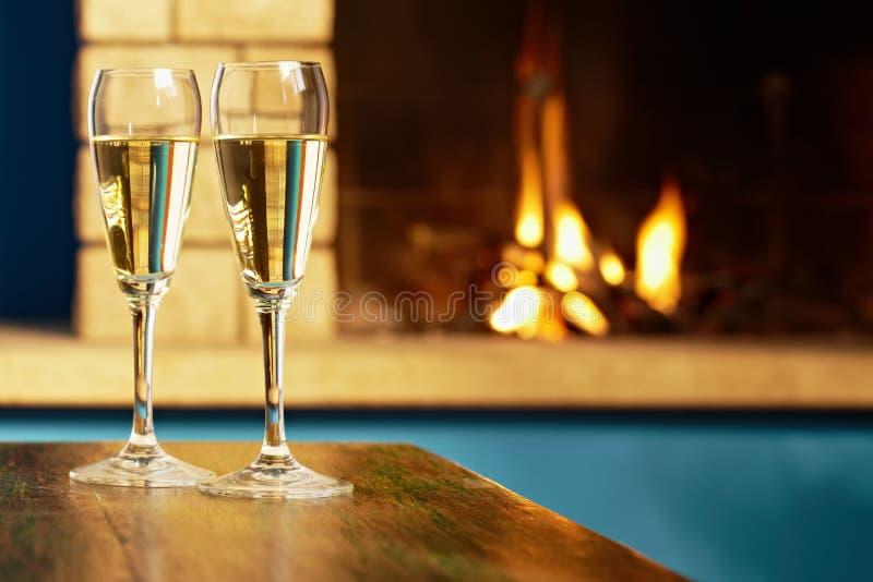 Dos flautas llenadas de champán cerca de la chimenea imagenes de archivo