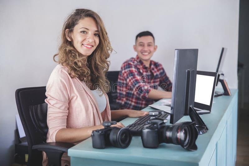 Dos fotógrafos que sonríen mientras que corrige las fotos en su ordenador fotos de archivo