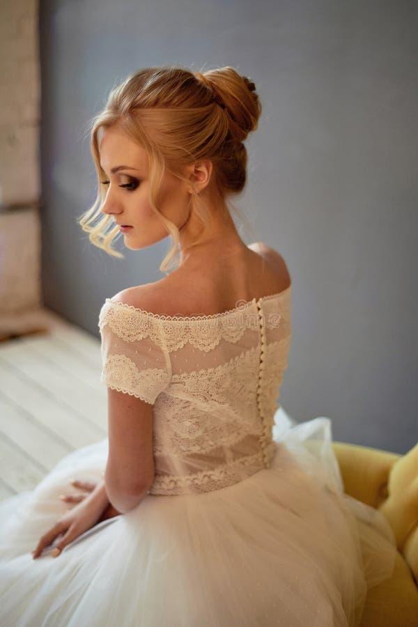 Dos fragile d'une fille dans une robe de dentelle avec une petite rang?e des boutons Tendresse pendant le matin de la jeune mari? image stock