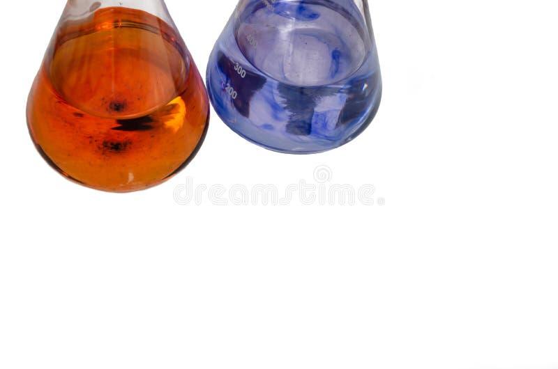 Dos frascos de laboratorio con líquidos mezclados con reactivo químico coloreado aislados en fondo blanco Cerrar Copiar espacio imagen de archivo