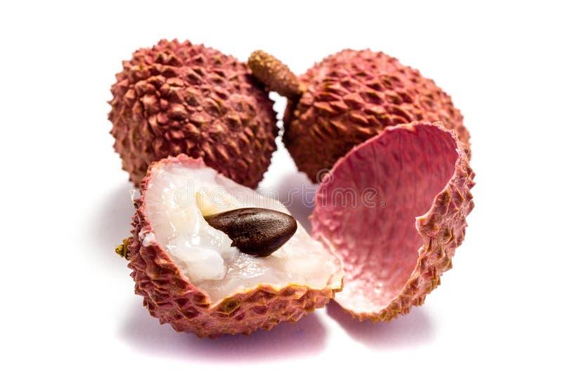 Dos frutas y una del lichí cortadas aislado en el fondo blanco foto de archivo