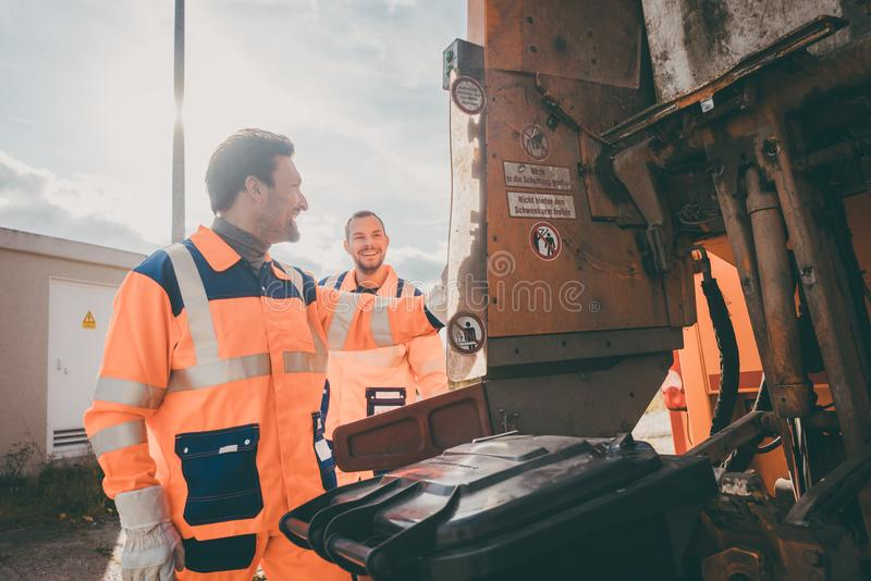 Dos garbagemen que trabajan junto en vaciar los cubos de basura fotografía de archivo