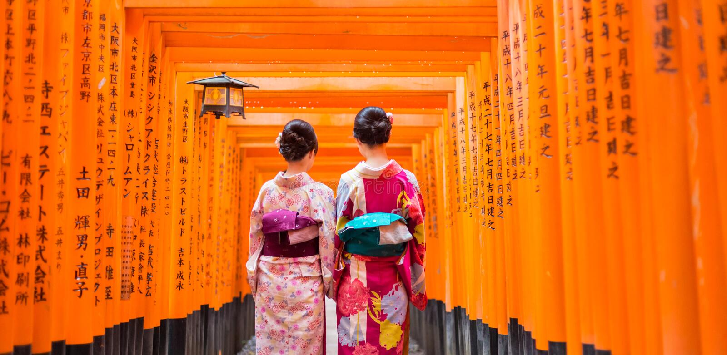 Dos geishas entre Tori Gate de madera roja en la capilla de Fushimi Inari en Kyoto, Japón imágenes de archivo libres de regalías