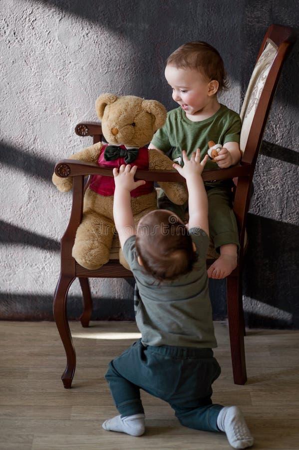 Dos gemelos de los muchachos a la edad de un año que se sienta después en la butaca fotografía de archivo
