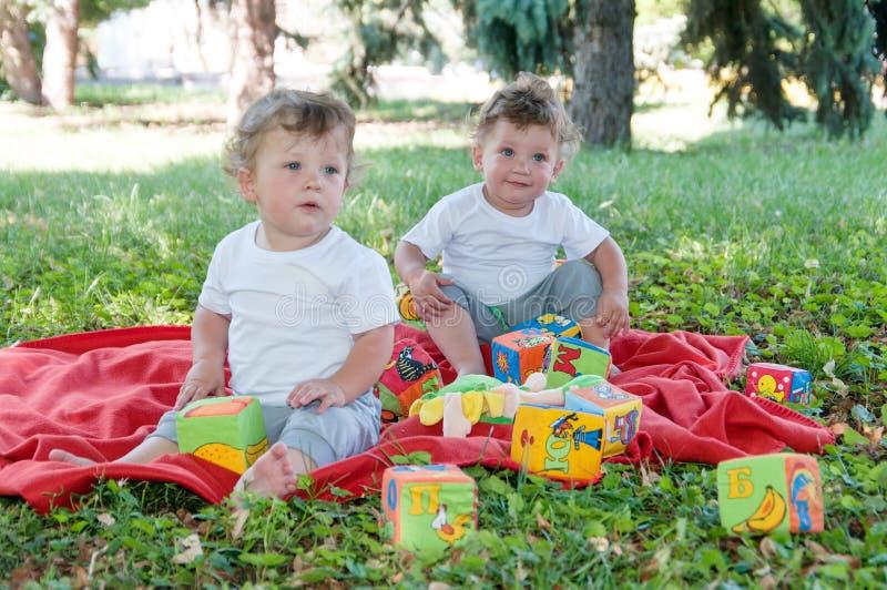 Dos gemelos de los muchachos que se sientan en una manta roja con los juguetes imagenes de archivo