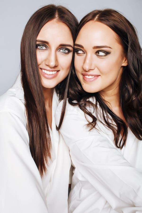 Dos gemelos presentación de las hermanas, haciendo la foto, vestida imagen de archivo
