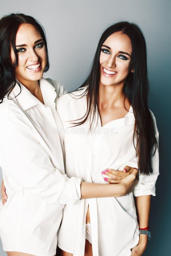Dos gemelos presentaci?n de las hermanas, haciendo el selfie de la foto, vistieron la camisa blanca, amigos diversos del peinado, imágenes de archivo libres de regalías