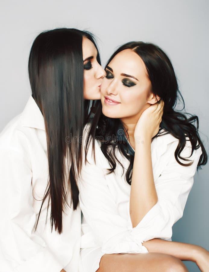 Dos gemelos presentaci?n de las hermanas, haciendo el selfie de la foto, vistieron la camisa blanca, amigos diversos del peinado, imagen de archivo libre de regalías