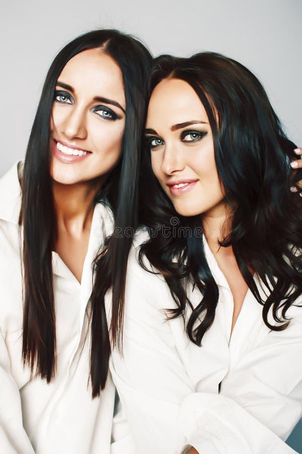 Dos gemelos presentaci?n de las hermanas, haciendo el selfie de la foto, vistieron la camisa blanca, amigos diversos del peinado, foto de archivo