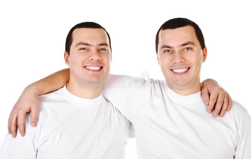 Dos gemelos sonrientes de los hombres jovenes del positivo atractivo imagen de archivo
