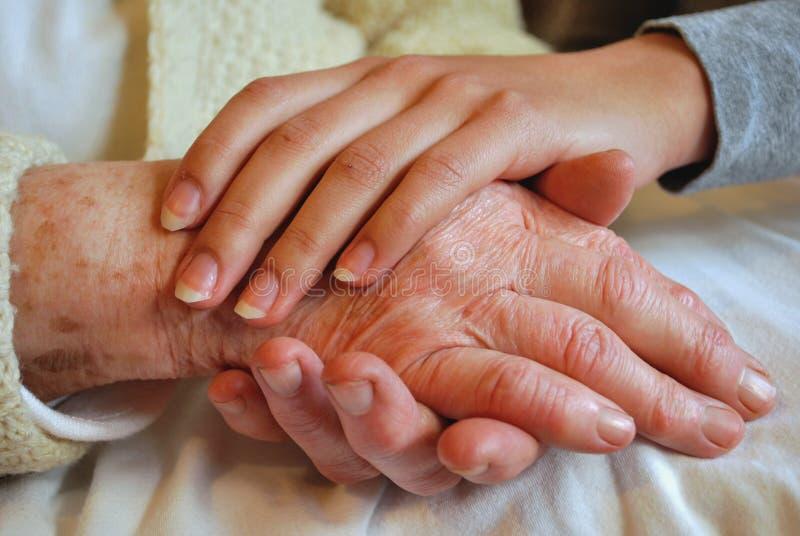 Dos generaciones que abrazan y que celebran las manos imagenes de archivo
